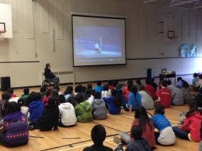 Student watch a video about Rick Hansen's Man in Motion tour during Chris Somerville's presentation.